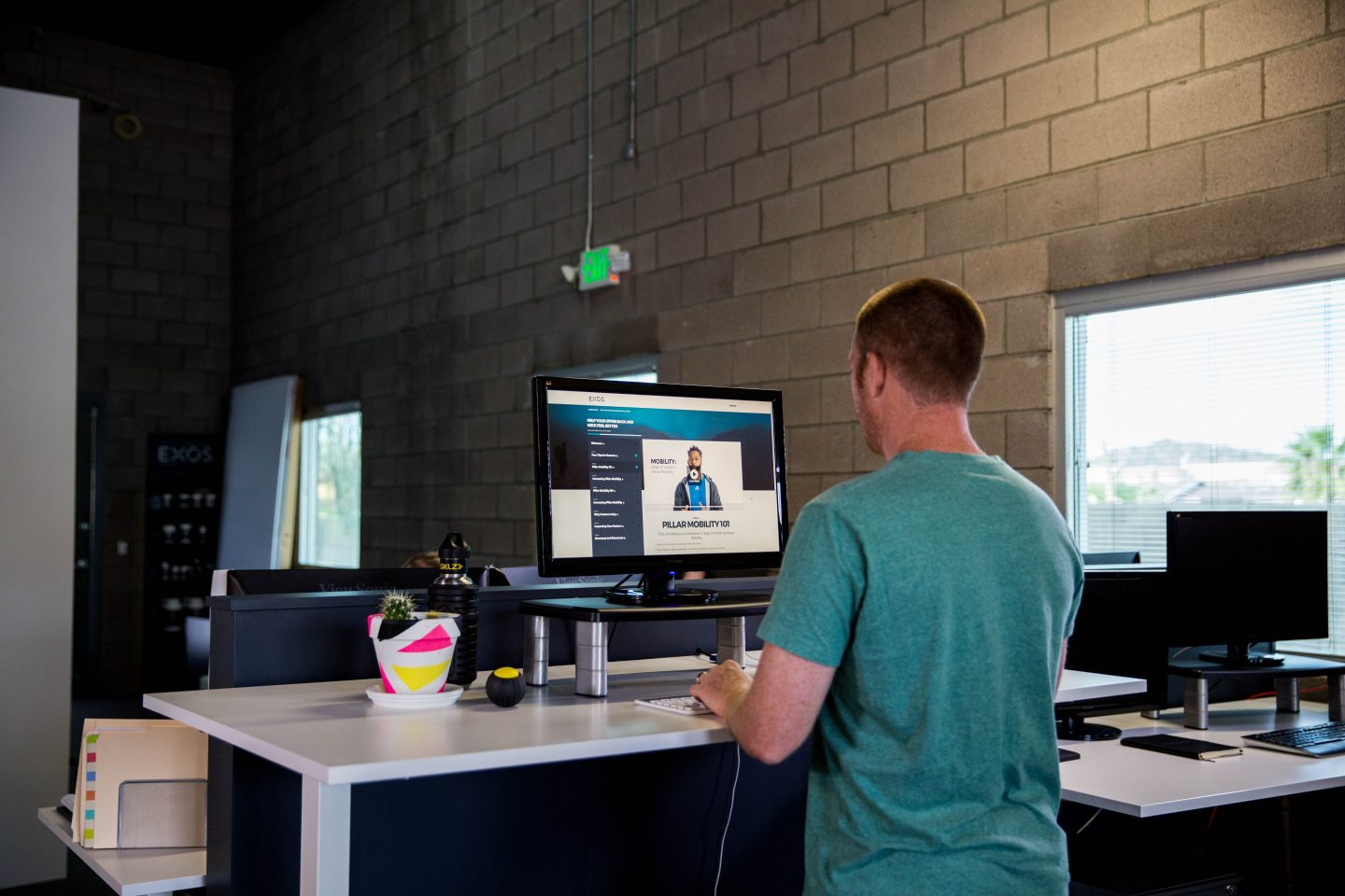 A man standing at a desk in a healthy position wearing t-shirt. standing desk, health, healthy work place, work space, mental health, productivity, EXOS, GamePlan A