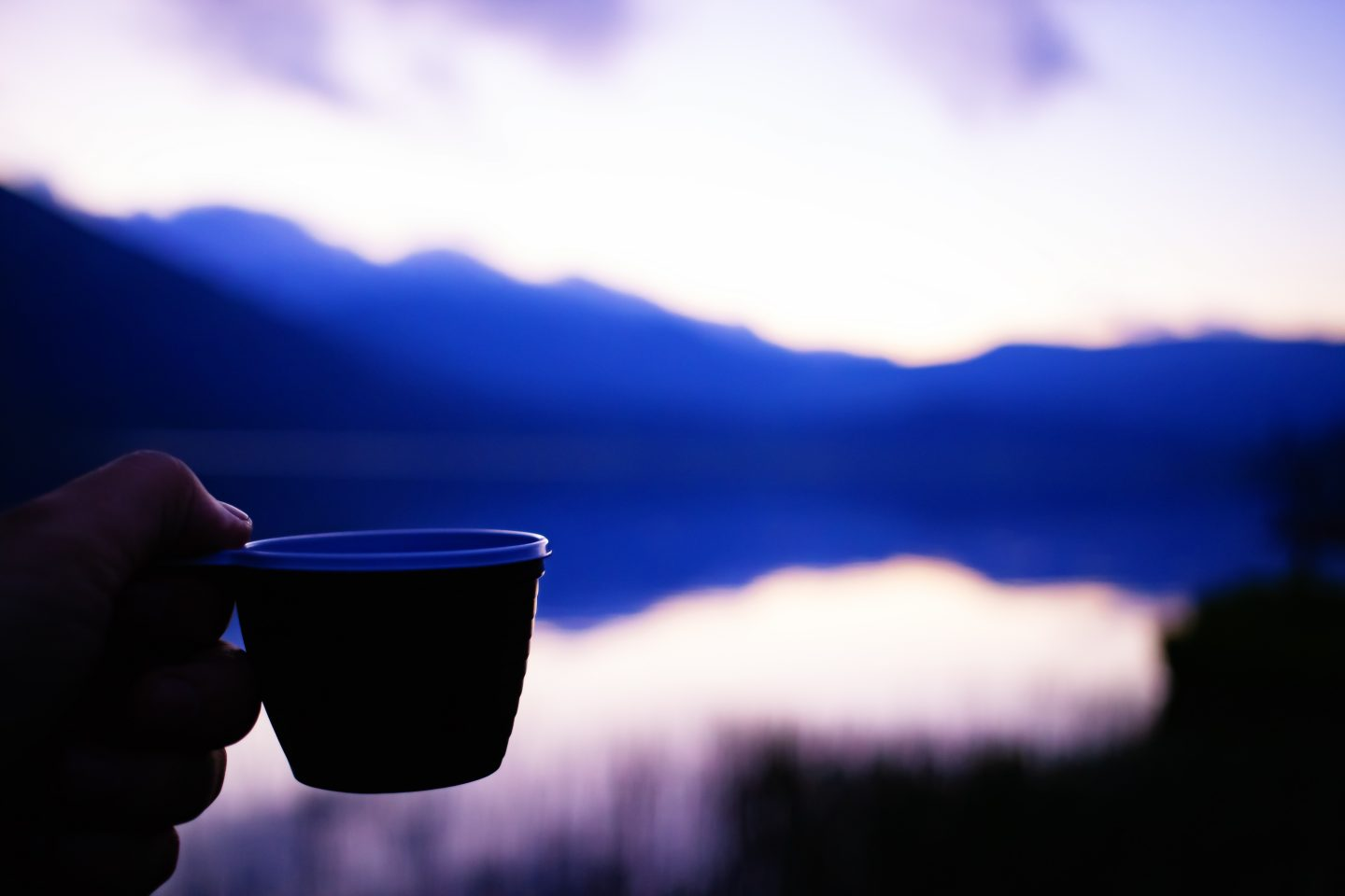 Cup of coffee in the hand of a traveler at sunset in the mountains near the lake. nutrition tips, healthy nutrition, fitness, outdoor, hiking, food, GamePlan A