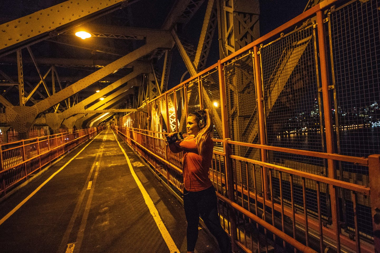 Woman stretching her muscles after a run at night on Brooklyn Bridge in New York, city run, sport, workout, after work exercise, inspiration, Brooklyn Bridge, New York, adidas, GamePlan A