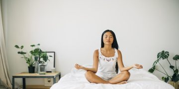 Woman sitting on bed cross-legged meditating, yoga, meditation, free your mind, Asana Sukhasana, adidas, GamePlan A
