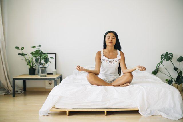 Woman sitting on bed cross-legged meditating, yoga, meditation, free your mind, Asana Sukhasana, adidas, GamePlan A