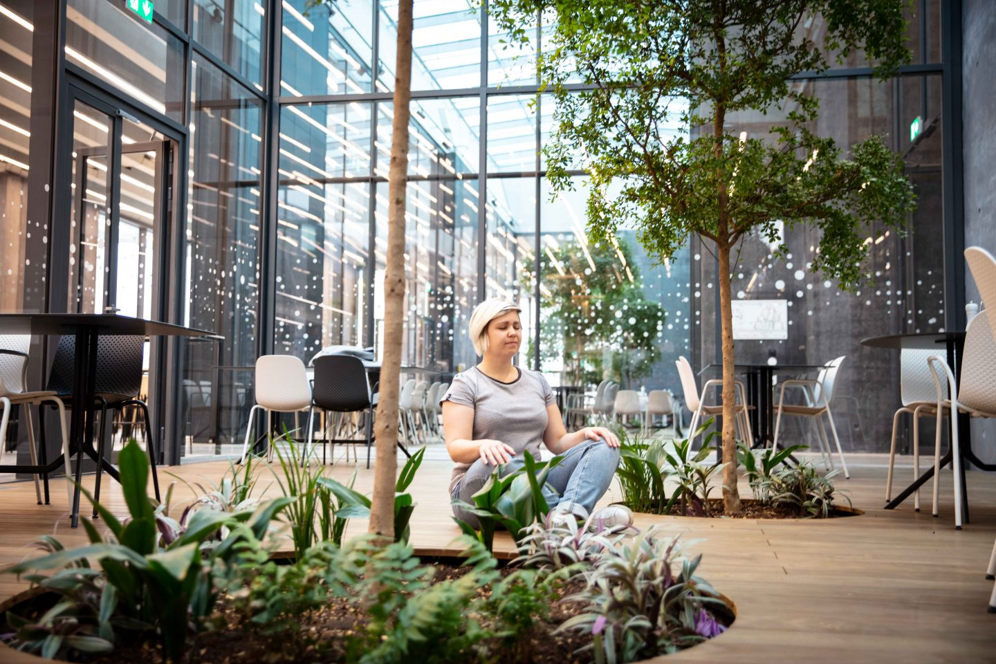 Woman sitting cross-legged in an open office space, work atmosphere, meditation, yoga, cross-legged, green space, adidas HQ, Herzogenaurach, GaamePlan A