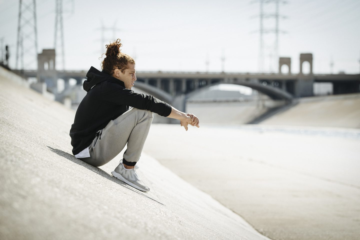 Guy wearing sports clothes sitting on concrete ramp with bridge in the backgruond, urban, urban athlete, workout, after workout, recovering, overview, take a breath, Reebok, GamePlan A
