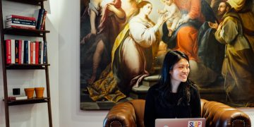 Woman sitting on a chair with a laptop smiling in front of a renaissance painting, Georgette Eva, Croissant app, co-working, creativity, inspiration, learning, new ideas, motivation, GamePlan A