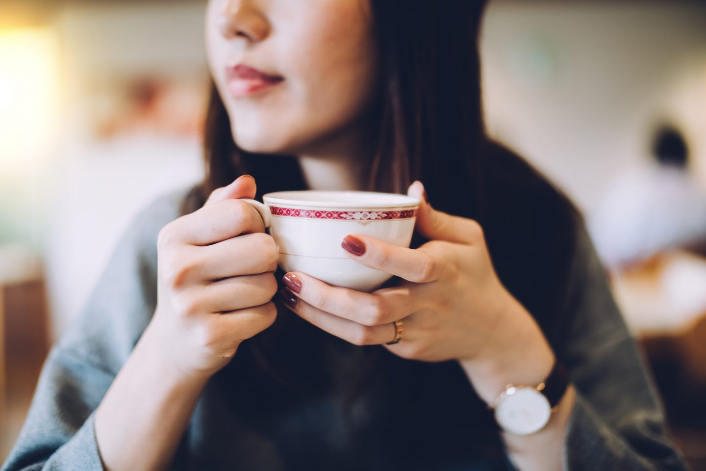 Woman with a watch holding teacup with red nail polish looking out of the window, calm, serene, relax, cafe, thinking, daydream, leisure, inspired, coffee, tea, GamePlan A