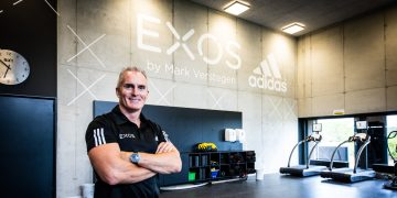 Mark Verstegen standing cross-armed and smiling in the gym. He is wearing a black polo short and is looking into the camera. EXOS, leadership, leadership skills, leadership advice