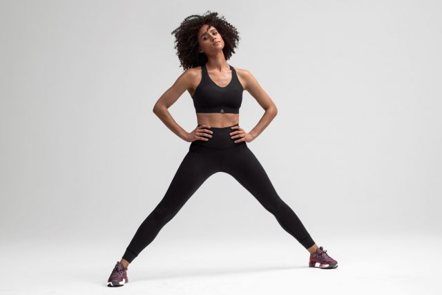 Woman stretching in black sportswear looking confident and strong, Nathalie Emmanuel, actress, sports, feminism, girl, Reebok, GamePlan A