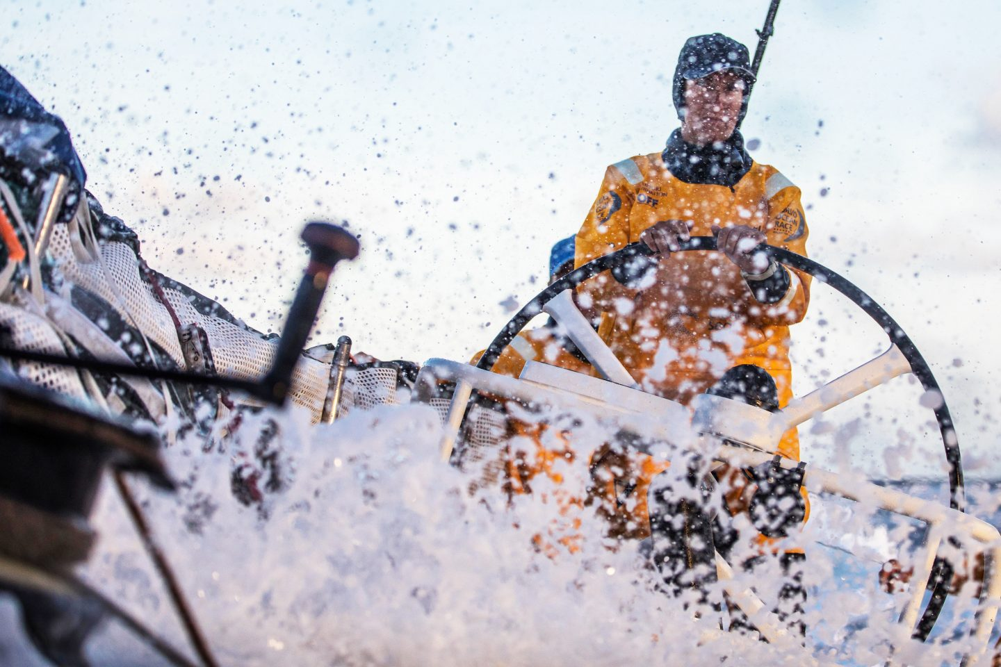 Woman in yellow outfit steering yacht with waves splashing, Dee Caffari, sailor, yachtswoman, leadership, confidence, inspirational, GamePlan A