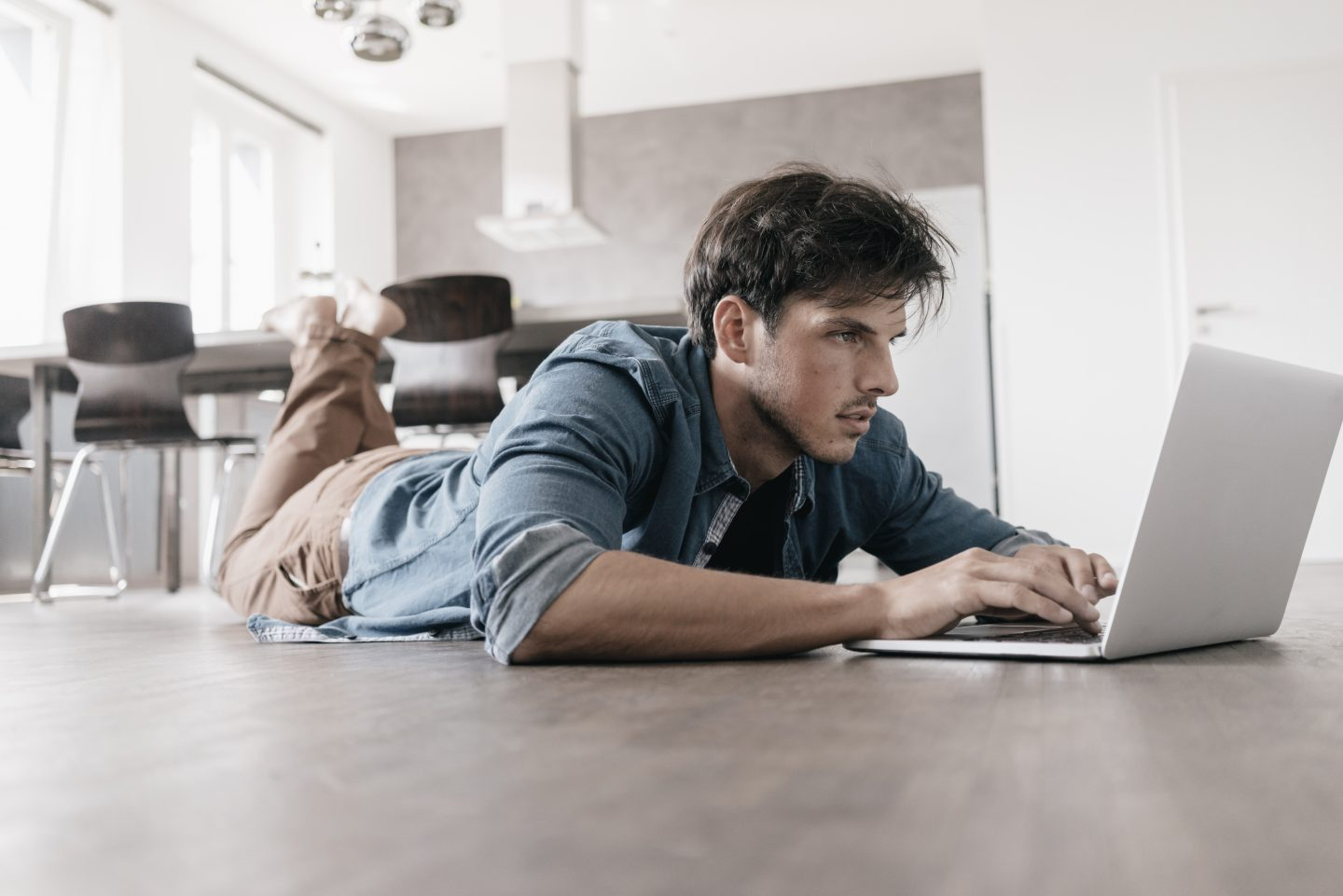 Man in blue shirt lying on the floor using laptop computer, working, studying, concentration, career, adidas, GamePlan A
