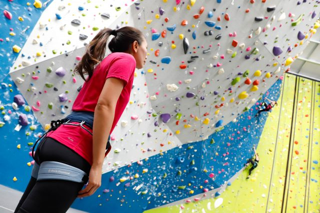 A woman standing on the ground and looking up to an indoor climbing wall. challenge, overcoming fear, self-reflection, self-improvement, leadership skills, confidence, GamePlan A