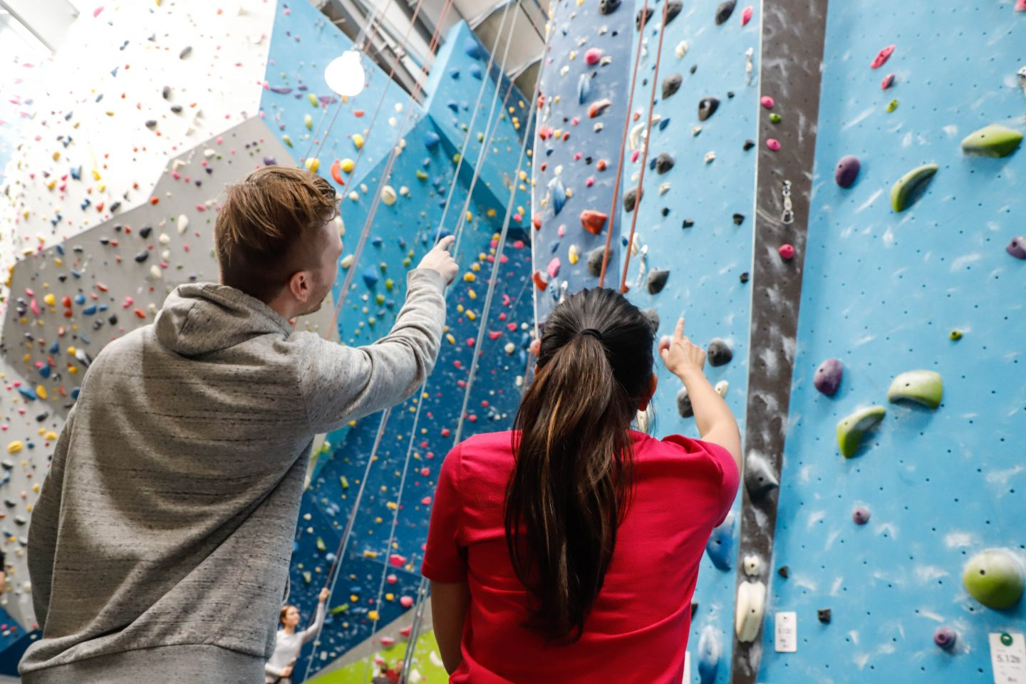 Two climbing partners look up to an indoor climbing wall and discussing the climbing route. challenge, overcoming fears, self-reflection, self-improvement, trust, leadership skills, GamePlan A