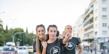 Girl in black adidas Runners t-shirt pointing into the distance with teammates behind her, team, goals, goal-setting, together, support, adidas, adidas Runners, sports, GamePlan A
