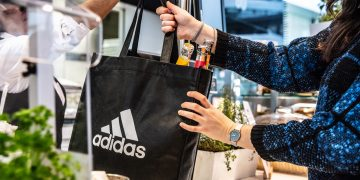 A person handing over a reusable adidas shopping bag. sustainability, avoiding plastic, GamePlan A