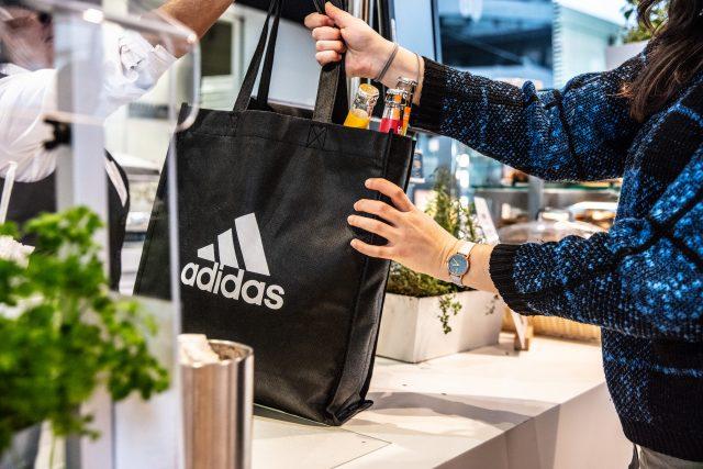 A person handing over a reusable adidas shopping bag. sustainability, avoiding plastic, GamePlan A