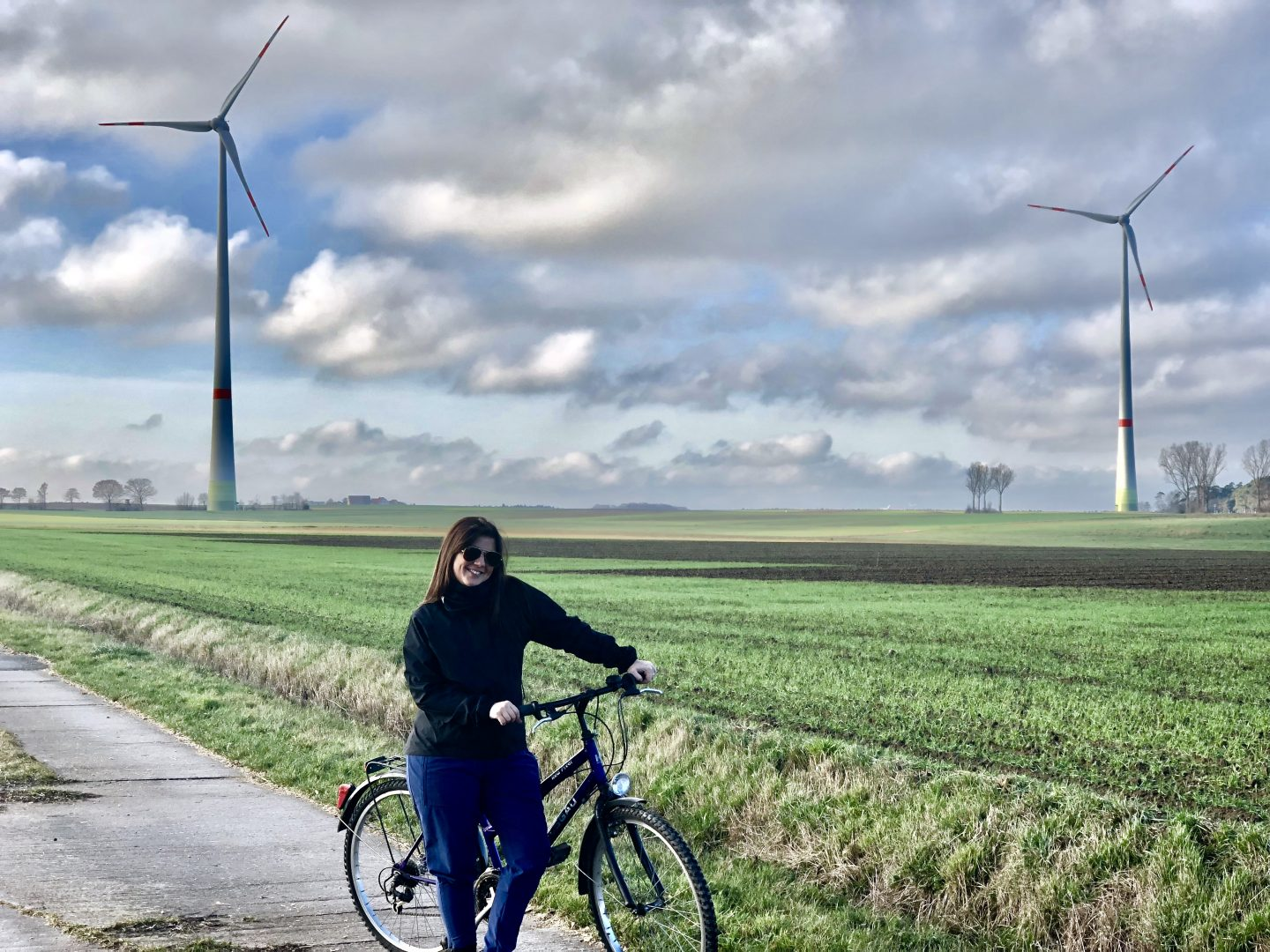 A person standing on a cycling track with her bike in front of wind wheels. sustainability, cycling to work, commuting, GamePlan A