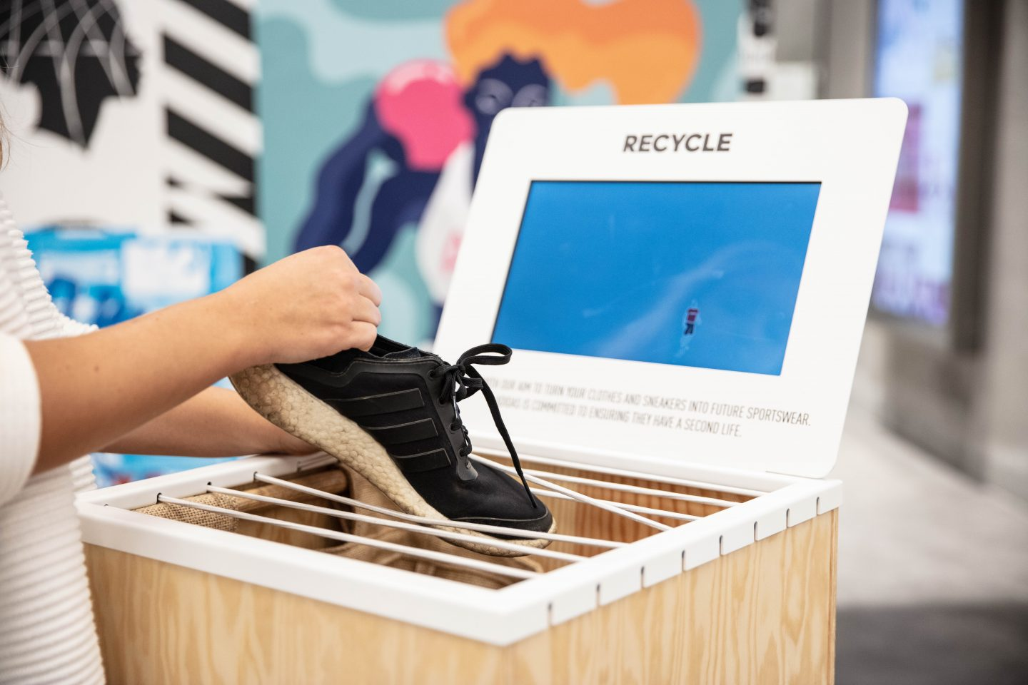 A woman putting an old adidas sneaker in a take back program box. sustainability, recycling, product take back program