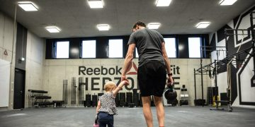 A father holding his toddler's hand carrying a kettlebell in a CrossFit box from behind.