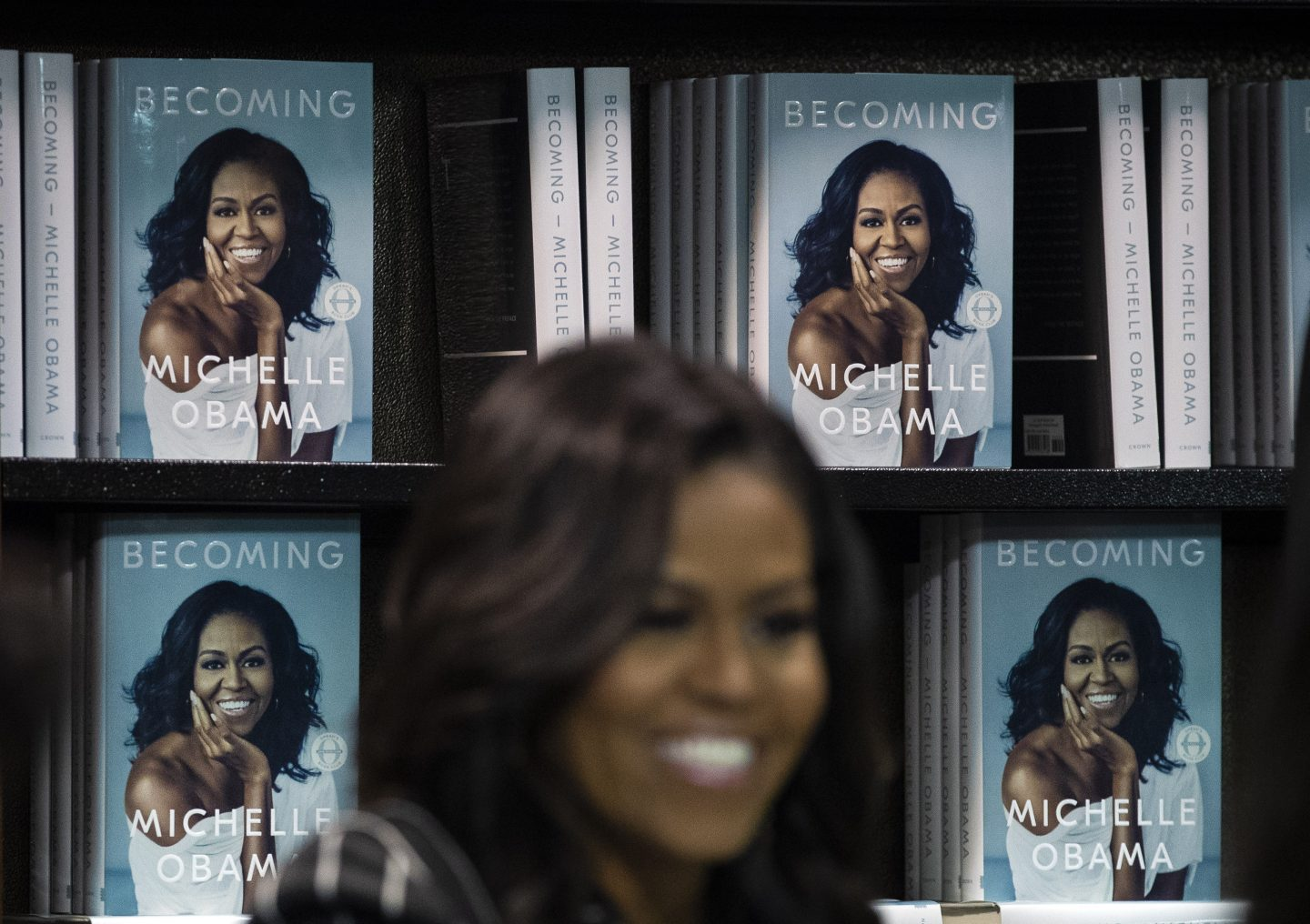 Michelle Obama standing in front of a wall of her books smiling. diversity, gender eguality, empowerment, women, GamePlan A, Reebok