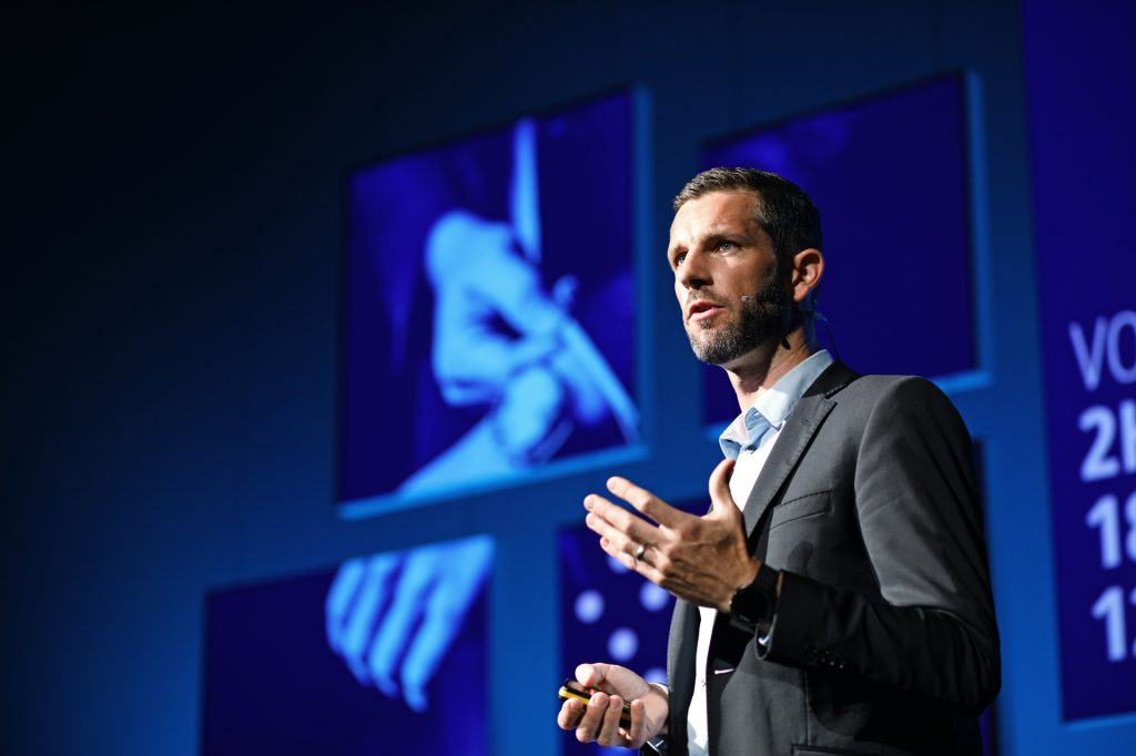 Florian Bernard speaking on stage using hand gestures for emphasis. pitching, public speaking, body language, performance, GamePlan A