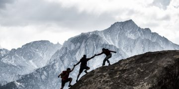 Three people are rock climbing in the mountains, helping each other building a chain to reach the top. reaching goals, team-work, bonding, collaborating, GamePlan A