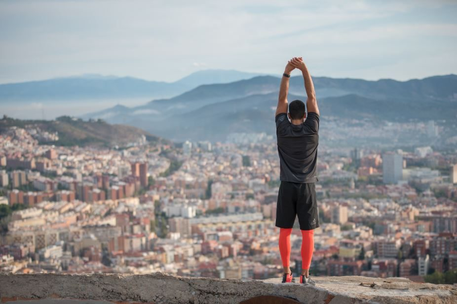 A man standing on a viewpoint looking down on a big city while stretching for a run.