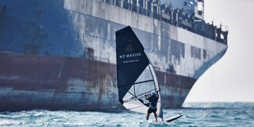 A windsurfer surfing in front of a big ship on the ocean. St. Regis Windsurfing with Nick Moloney to Macau, motivation, success, career, GamePlanA