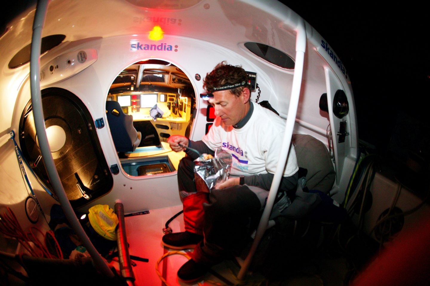 A sailor wearing a headlamp eating on board of his sailboat. Nick Moloney, sailing, career, motivation, preparation, success, mindset, GamePlan A