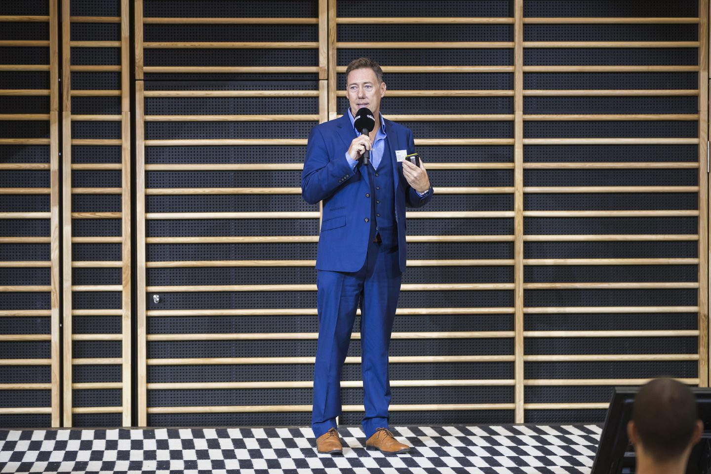 A man wearing a blue suit standing on stage and talking into a microphone. Nick Moloney, career, success, mindset, motivation, adidas HQ, GamePlan A