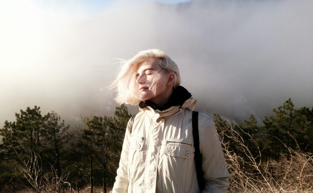 A woman standing on top of a mountain surrounded by fog and wind, closing her eyes to feel the sun on her face. Letting go, balance, lifestyle, happiness, GamePlan A