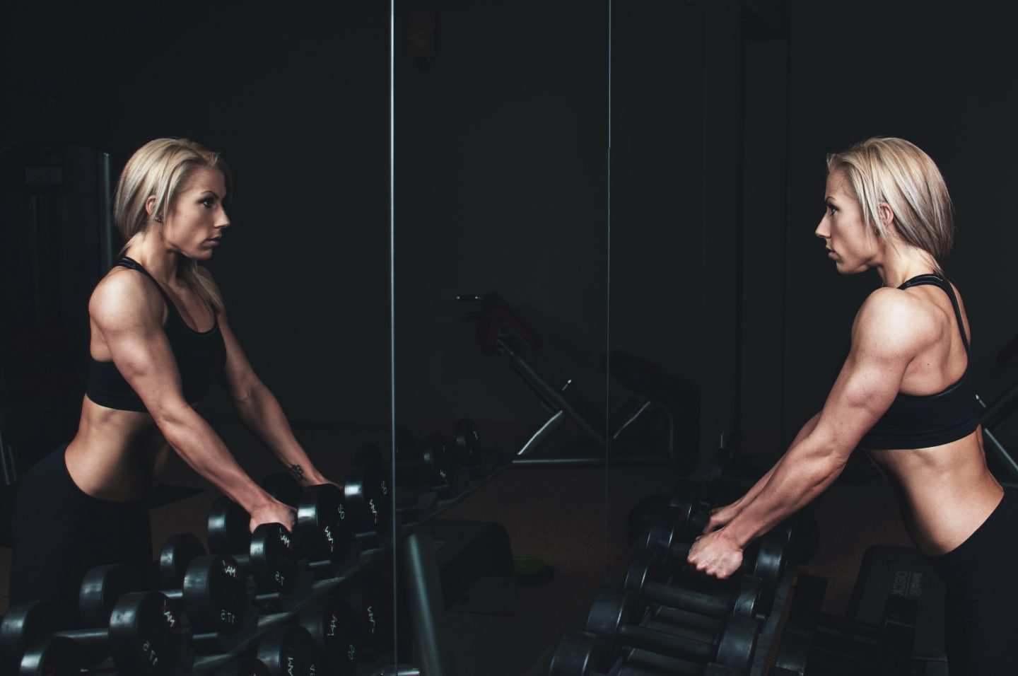 A strong woman looking at her reflection in the mirror in a dark gym, holding weights. self-reflection, self-awareness, body shape, fitness, GamePlan A.