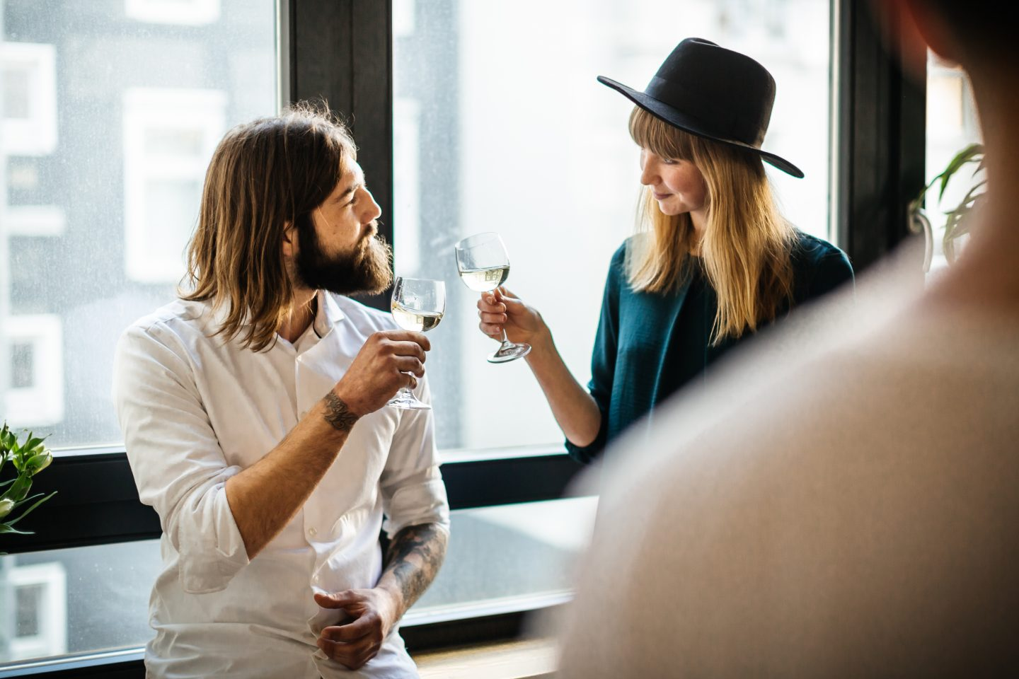 Two friends standing close toasting with glasses of wine. Balance, enjoying life, healthy lifestyle, trade-offs, GamePlan A.