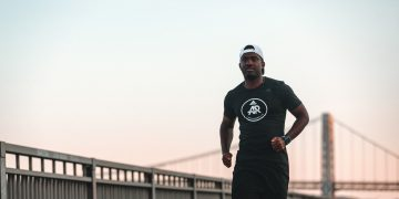 Man running along a river in the city at sunset. adidas Runners, city running, determination, marathon training, GamePlan A.