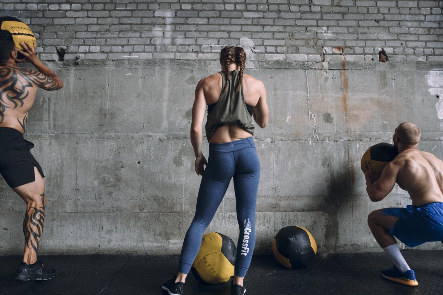 A woman standing between two men in front of a concrete wall wearing CrossFit outfits and doing wall balls. Reebok, training, coaching, fitness, leadership, team, Reebok