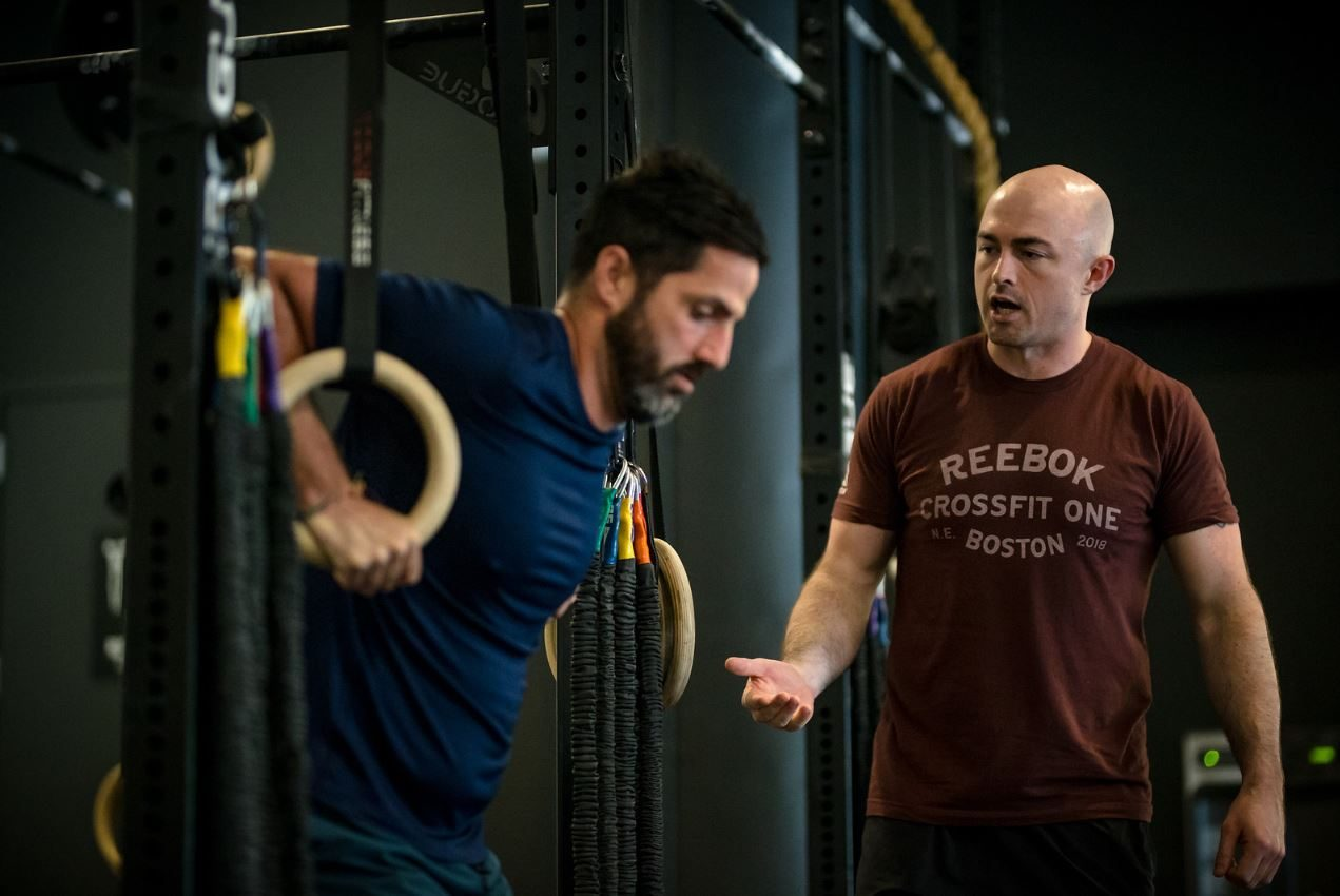 A coach is motivating a man, who is doing muscle ups in the gym. leadership, coaching, CrossFit, Reebok, motivation, team, teamwork, success, GamePlan A