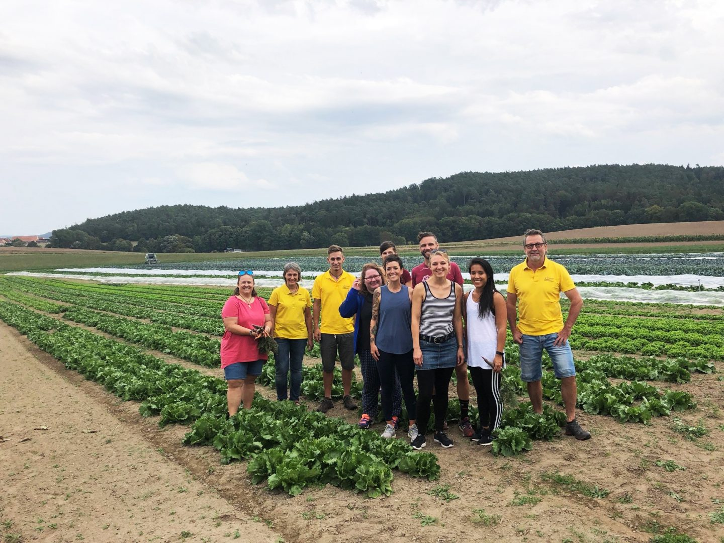 A group of people standing on a field and smiling into the camera. employees, sustainability, farming, career advice, purpose, GamePlan A