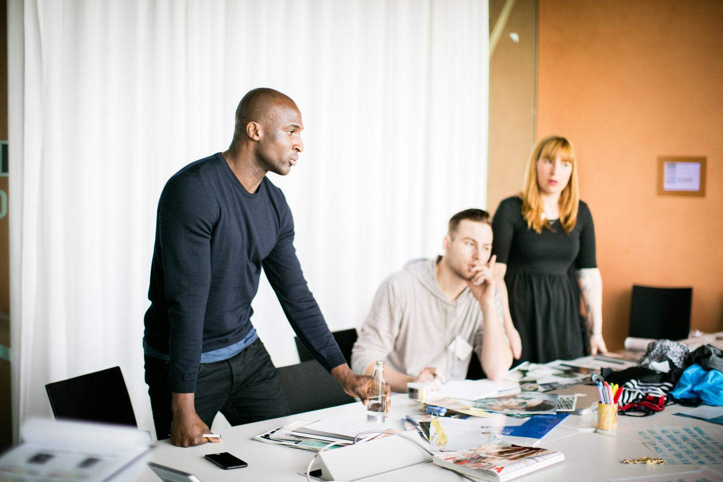 A team at a large office table holding a meeting. coaching, leadership, team, role model, GamePlan A