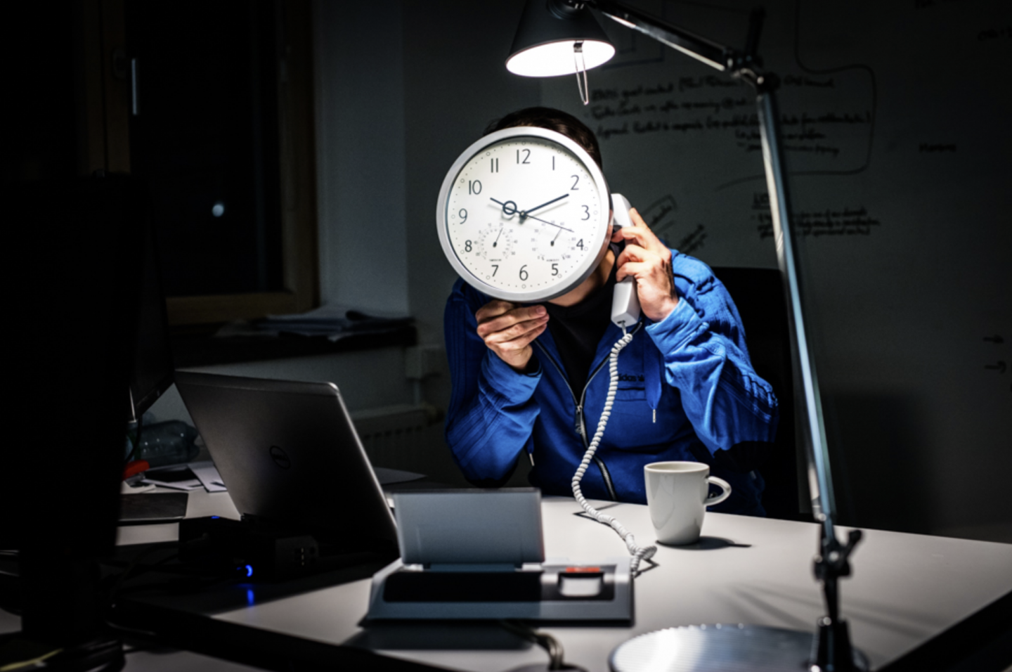 An employee sitting at his office desk late at night, talking on the phone, with a big clock in front of his face. over hours, time management, work-life-balance, performance, GamePlan A
