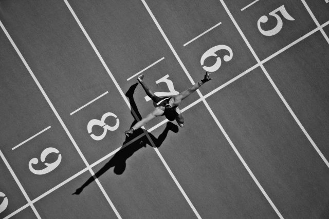 Runner crossing the finish line on the track. goal, sprinting, running, achieving, GamePlan A