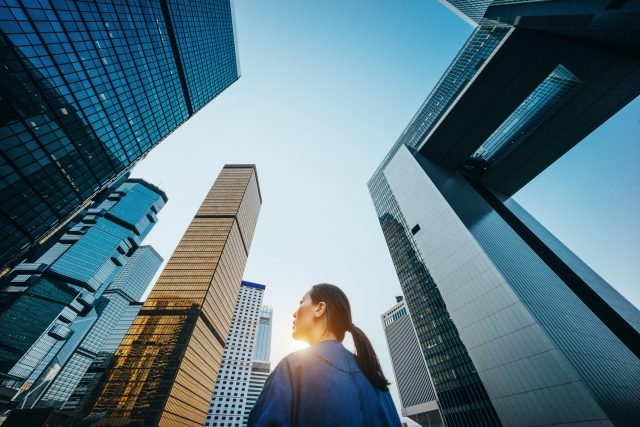 Low angle view of woman standing against modern skyscrapers and blue sky in city at sunrise. relocation, city, confidence, international, working abroad, GamePlan A