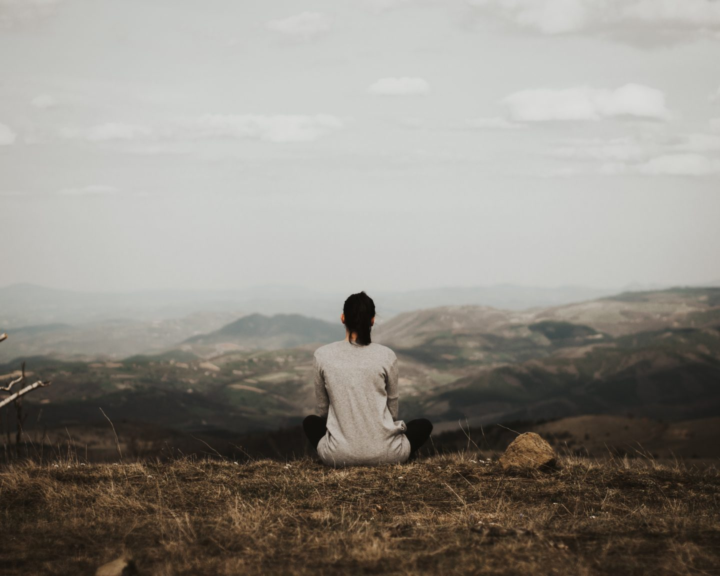 A girl sitting on the ground enjoying the view into the mountains while letting her mind wander.