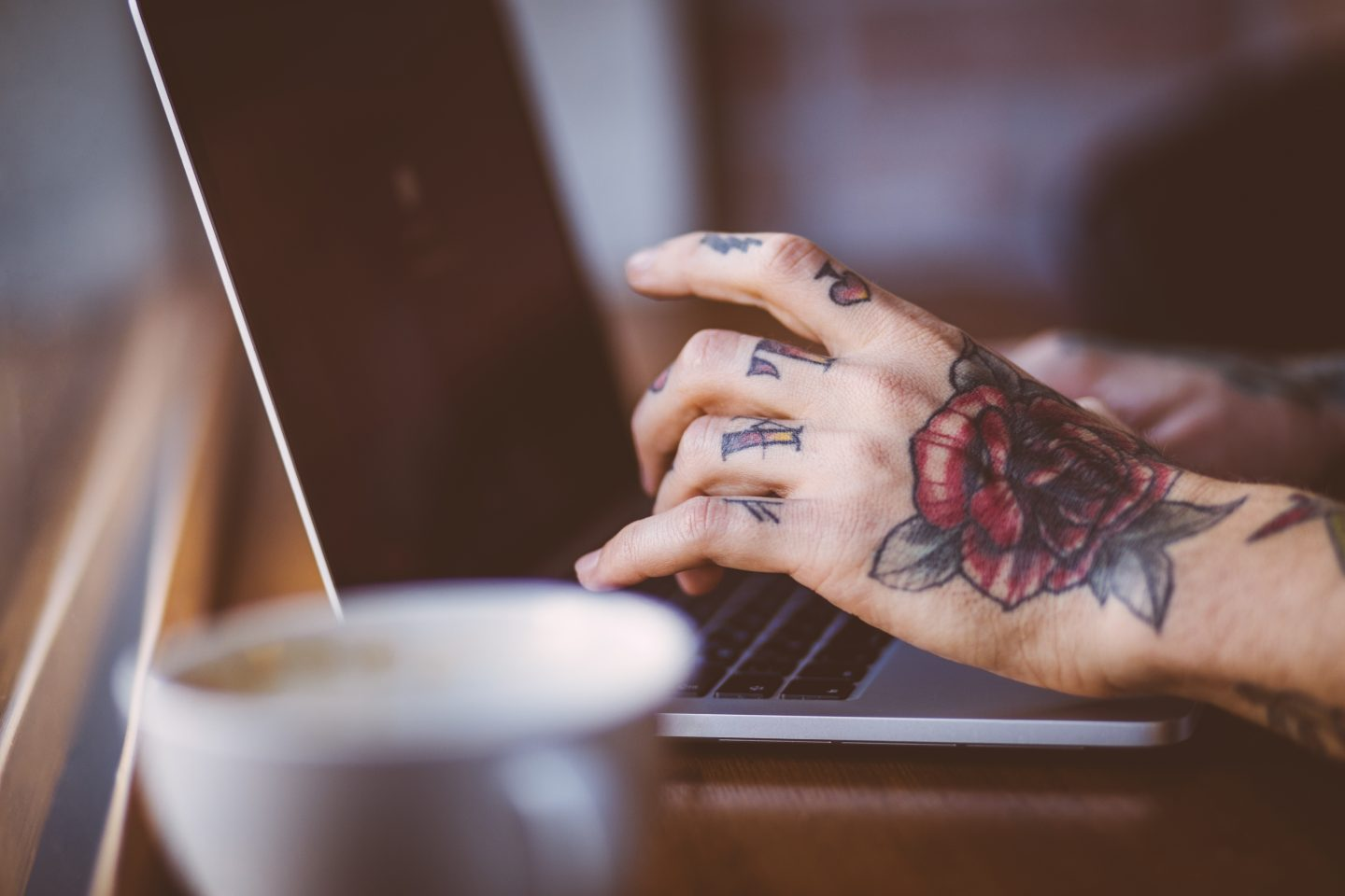 Close up of man's hands with tattoos typing on keyboard