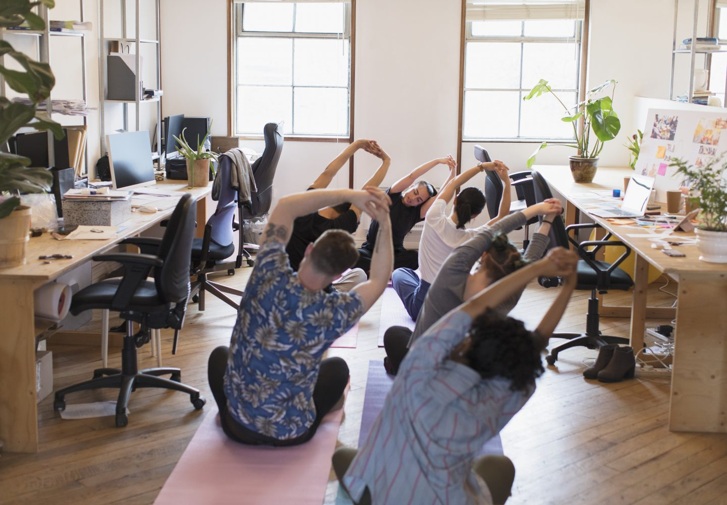 Creative business people stretching, practicing yoga as part of their employers wellness program in the office.