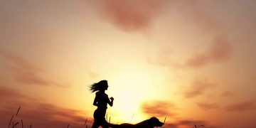 A female runner and a dog running against a sunset sky. dog running, purpose-driven life, fitness