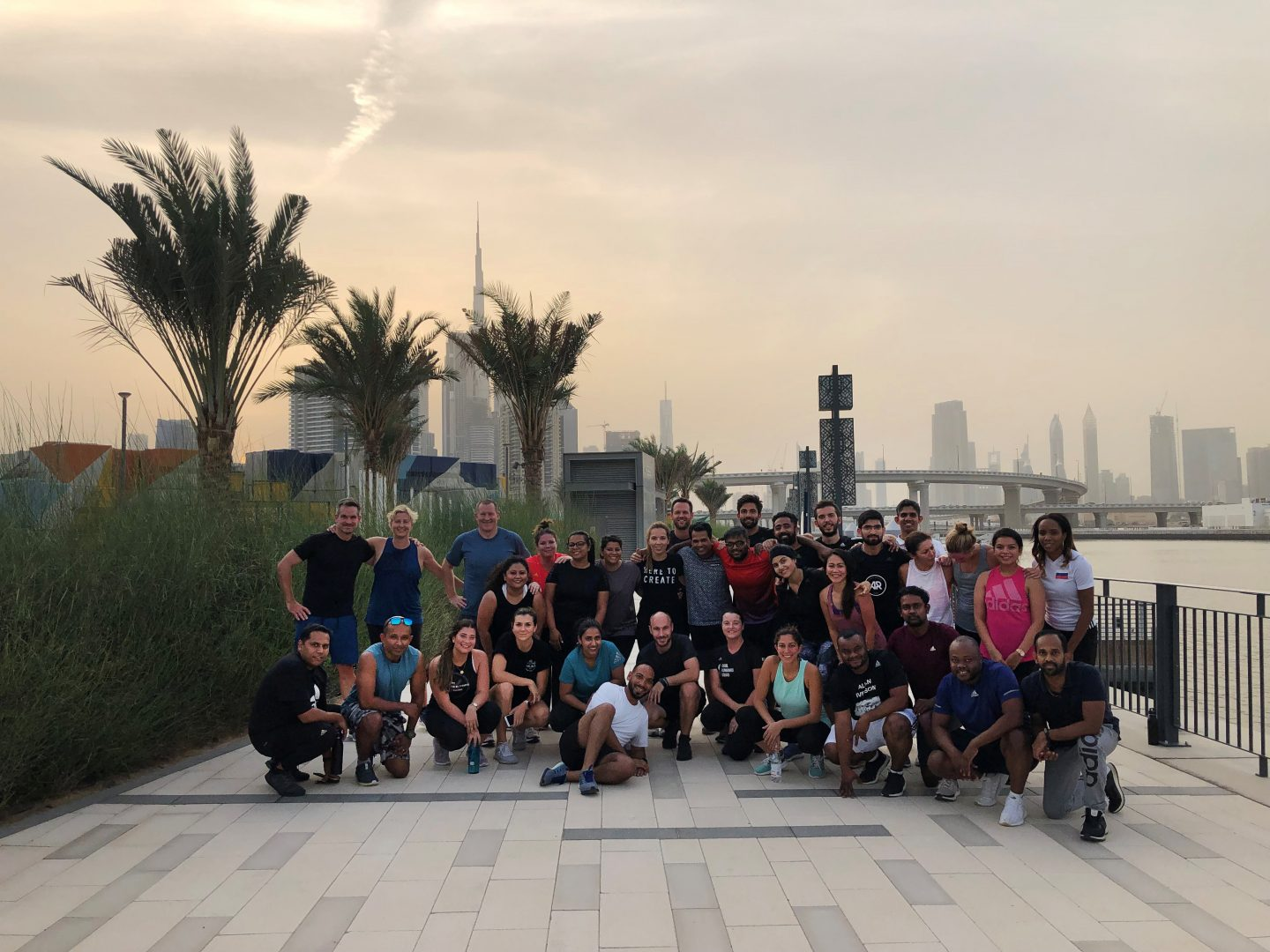 A group of runners standing together for a group picture in front of a city skyline. winning culture, motivation, success, personal growth