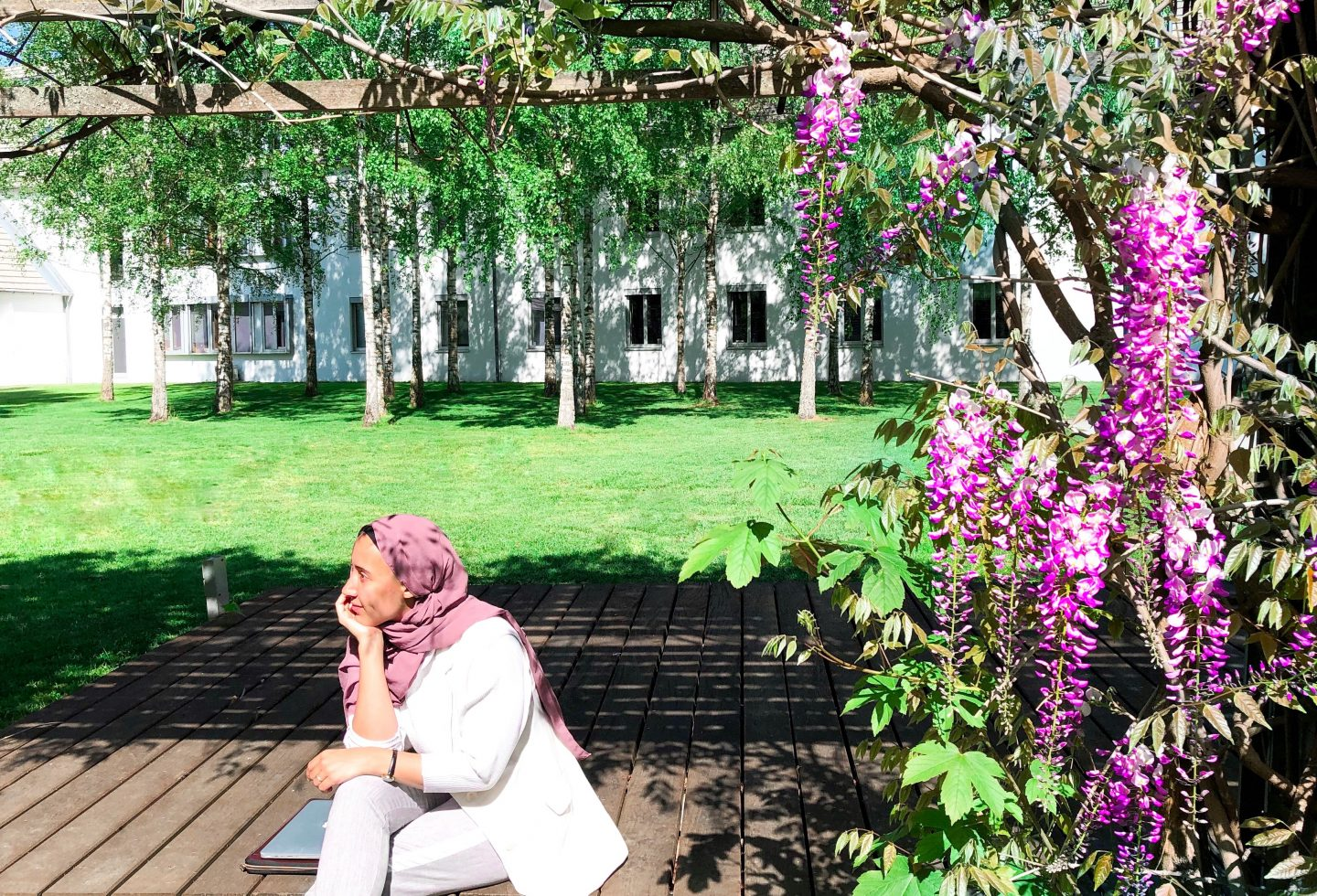 Sina Port, young woman with hijab at Adidas Headquarter sitting outdoors with flowers and office buildings around her