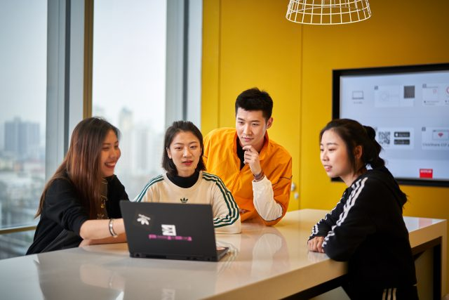 Group of chinese adidas employees at a meeting while giving each other feedback