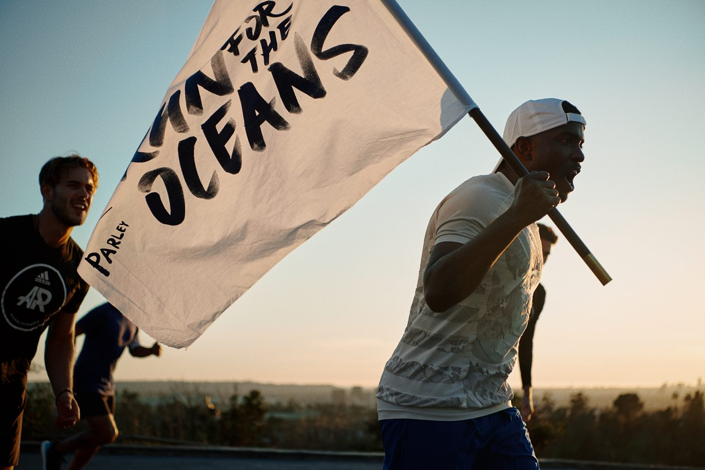 A man runs carrying a flag that says Run for the Oceans. Sustainable fashion, Gameplan A.