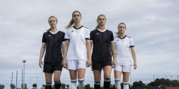 Four female soccer players walking towards you wearing white and black soccer kits. girls in sport, diversity, female athletes, Womens World Cup 2019, empowerment