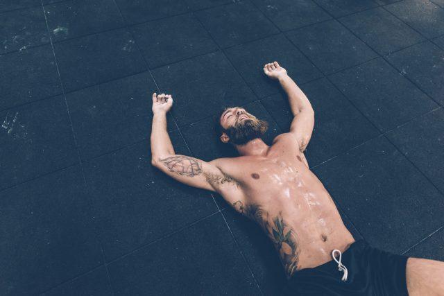 Exhausted male cross trainer lying on gym floor, great leader, leadership, fitness, leadership skills, GamePlan A