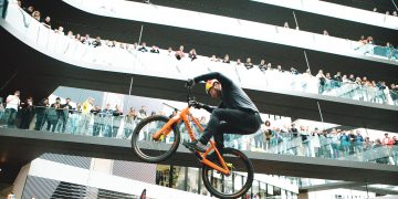 Mountainbike pro Danny MacAskill is performing a stunt in the Laces building at the adidas HQ